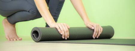 Young Asian woman concentrates on rolling black yoga mat after yoga class, close up shot.