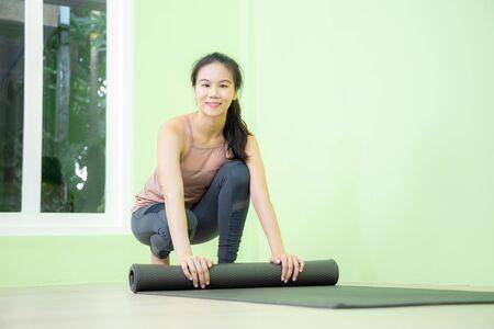 Young beautiful smiling Asian woman rolls yoga mat after finish yoga practicing in green wall studio, yoga class concept.