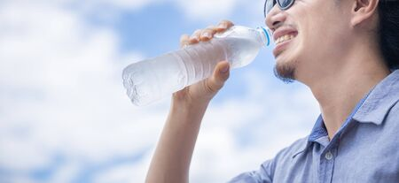 Panoramic photo of a happy business man with sun glasses drink cold water from plastic bottle during summer in day time and bright beautiful blue sky, hydration and health concept. Banco de Imagens