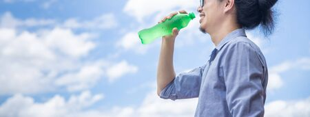 Panoramic shot of a happy business man with sunglasses holding green plastic bottle and drink water during summer in day time and bright beautiful blue sky, hydration and health concept with copy space.