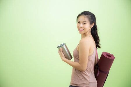 Happy young beautiful Asian lady carrying purple yoga mat while holding stainless tumbler stainless glass in another hand, looking back and smile while entering studio for practicing. Stockfoto