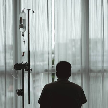 Silhouette male worried patient sitting and look out the hospital window while having medical recovery treatment.