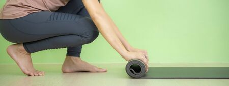 Young Asian woman concentrates on rolling black yoga mat after yoga class. Banner size. Banco de Imagens
