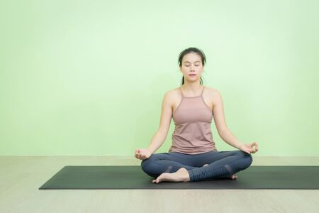 Beautiful smiling Asian woman sitting on black mat in lotus posture yoga, beginning relaxation for meditation and exercise in the room with green background wall.