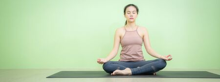 Banner photo of Asian woman sitting on black mat in lotus posture yoga, beginning relaxation for meditation and exercise in the room with green background wall. Stockfoto