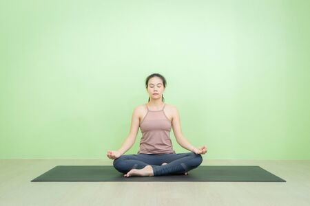 Asian woman sitting in lotus posture yoga, beginning relaxation for meditation and exercise in the room with green background wall. Stockfoto