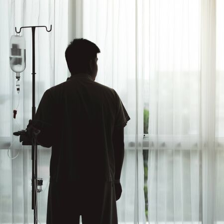Silhouette adult patient stand and hold infusion hanger pole looking out the hospital window, thinking about medical expenses and health care insurance. Фото со стока