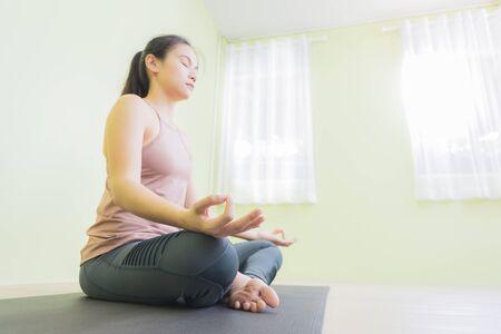 Asian woman sitting in lotus pose in yoga studio, low angle.