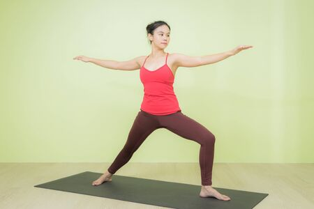 Young and beautiful sweaty Asian female instructor in sporty red colour cloth practicing in warrior pose on a black mat quietly in the room. Stockfoto