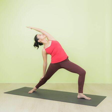 Young and beautiful sweaty Asian female instructor in sporty red colour cloth practicing in warrior pose on a black mat in gym.
