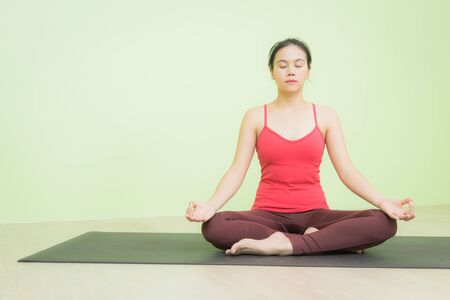 Happy and peacefully young Asian woman in bright red cloth sitting on black yoga mat practicing meditation in Lotus pose yoga. Stockfoto