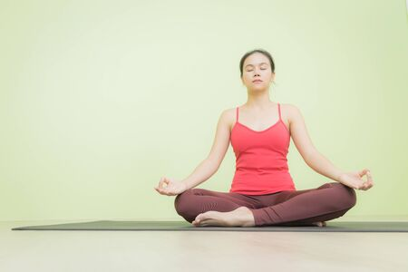 Happy and peacefully young Asian woman in bright red cloth sitting on black yoga mat practicing meditation in Lotus pose yoga, low angle