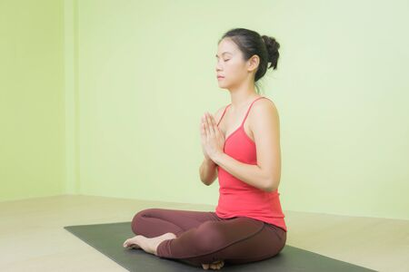 Happy and peacefully young Asian woman in bright red cloth sitting on black yoga mat practicing Namaste meditation in Lotus pose yoga.