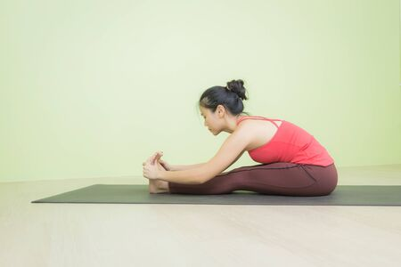 Young attractive Asian woman wearing red sportswear, brown pants, sitting in Seated forward bend exercise,  yoga pose, indoor shot. Stockfoto