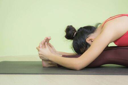 Close up of young attractive Asian woman wearing red sportswear, brown pants, sitting in Seated forward bend exercise,  yoga pose with face down, indoor shot.