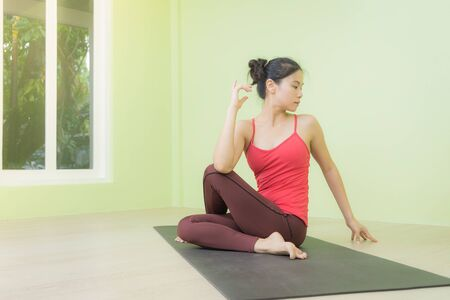 Attractive Asian woman wearing sportswear, red top, brown pants practicing in Ardha Matsyendrasana pose, Half Lord of the fishes pose, looking to the right in a yoga studio, indoor shot.