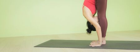 Young Asian woman  wearing sportswear, red top, brown pants practicing yoga on black mat against green wall yoga studio, doing Standing forward bend pose, head to knees,  indoor shot, banner size