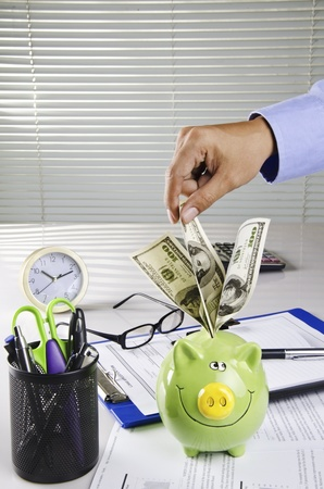 businessman saving money on his desk photo