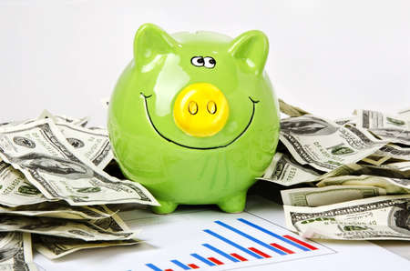 green piggy bank with dollars on bar chart Stock Photo
