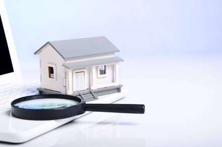 magnifying glass and model house on laptop