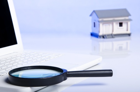 black magnifying glass on laptop and a model house photo