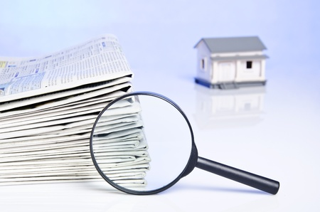 Finding a dreamed house on newspaper with blue background Stock Photo