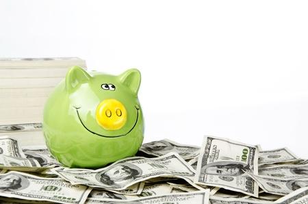 Green piggy bank on hundred of US dollars