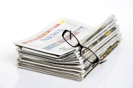 bird eye view of glasses on newspapers against white background Standard-Bild