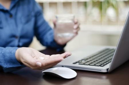 Une femme de prendre une pilule alors qu'elle travaille Banque d'images - 14168217