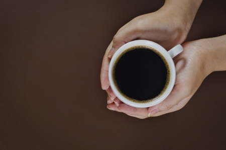 woman hand holding a cup of coffee photo