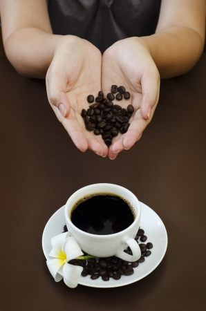 a young female holding coffee bean