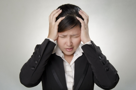 a business woman touching her head because of headache photo