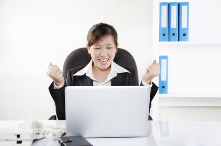 A pretty woman showing her excitement while looking at her laptop