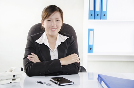 A business person smiling and hand crossed in the office