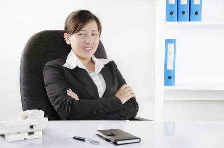 Business person sitting in the desk with arms crossed photo