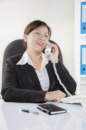 Young adult talking on the phone in office photo