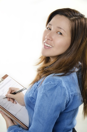 Beautiful businesswoman writing on her file photo