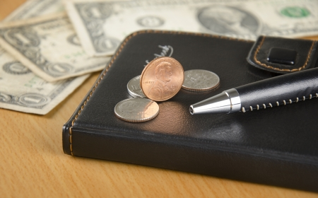 Notebook, US coins and office supply on the desk Stock Photo