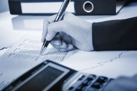 hand holding pen: Businesswoman is calculating numerical report