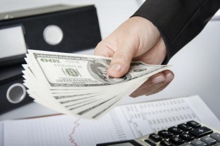 Businesswoman giving money of US dollars Stock Photo