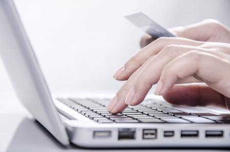 Les jeunes femmes mains tenant une carte de crédit et en entrant sur le clavier Banque d'images