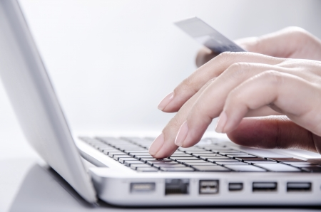 data entry: Young female hands holding credit card and entering on keyboard
