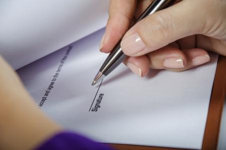 signing: Giovane donna di firmare un documento Archivio Fotografico