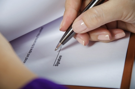 autograph: Young woman signing a document