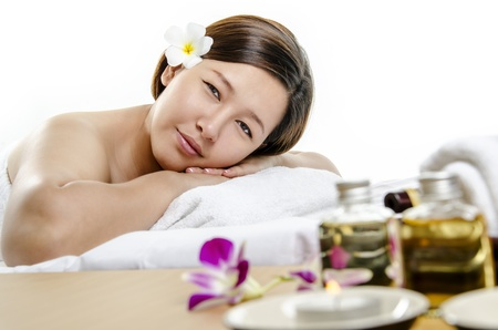 Closeup of young lady at spa and massage against white background photo