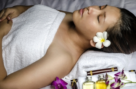 Portrait of young woman relaxing at spa and massage photo