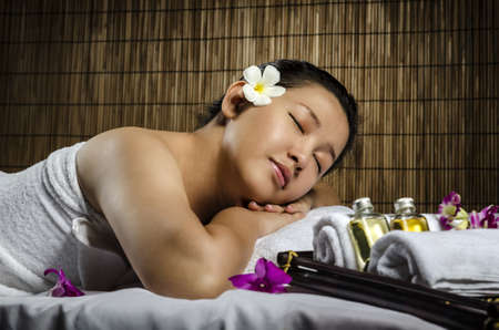 Portrait of fresh and beautiful woman laying on spa and massage photo