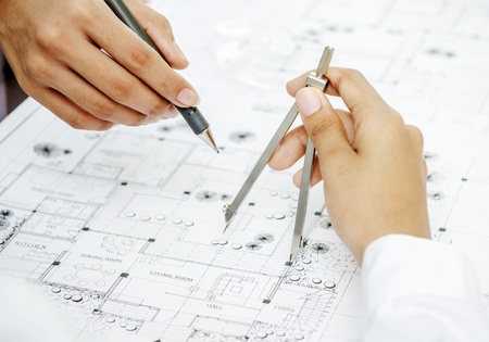 drawing compass: Architect reviewing blueprint by adjusting drawing compass