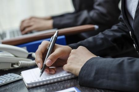 Geschäftspersonen, die auf dem Schreibtisch im Büro Standard-Bild - 21958373
