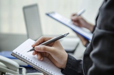 Business people taking note in office Standard-Bild